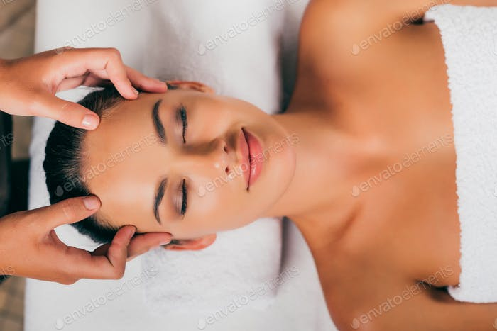 smiling woman relaxing in massage salon