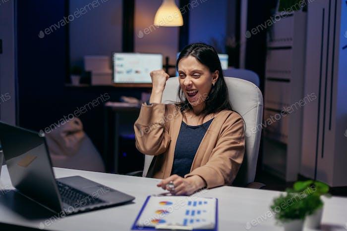Cheerful entrepreneur, feel ecstatic reading great online news on laptop