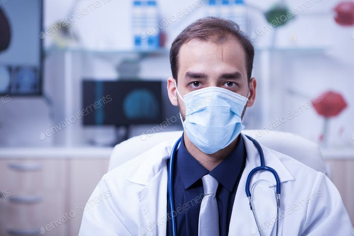 Portrait of serious doctor wearing a protection mask over his mouth