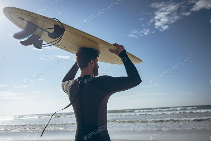 Rear view of young Caucasian male surfer holding surfboard on his head at beach on a sunny day