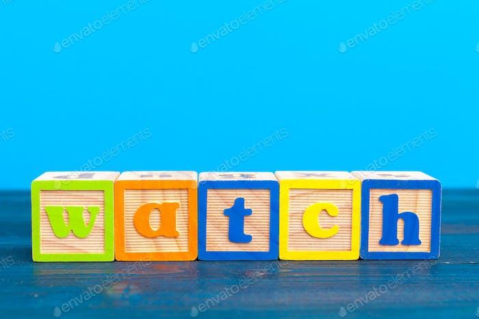 bloque de madera cubo con alfabeto construyendo la palabra reloj