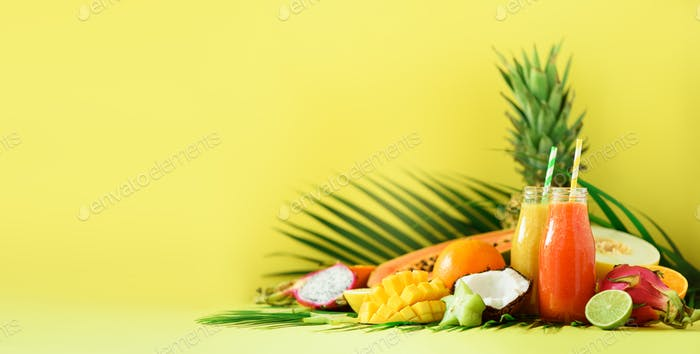 Juicy papaya and pineapple, mango, orange fruit smoothie in two jars on yellow background. Banner
