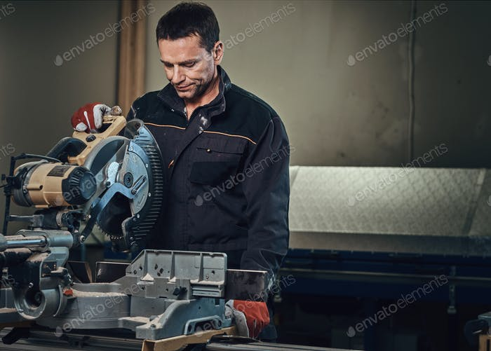 A man works with circular saw.