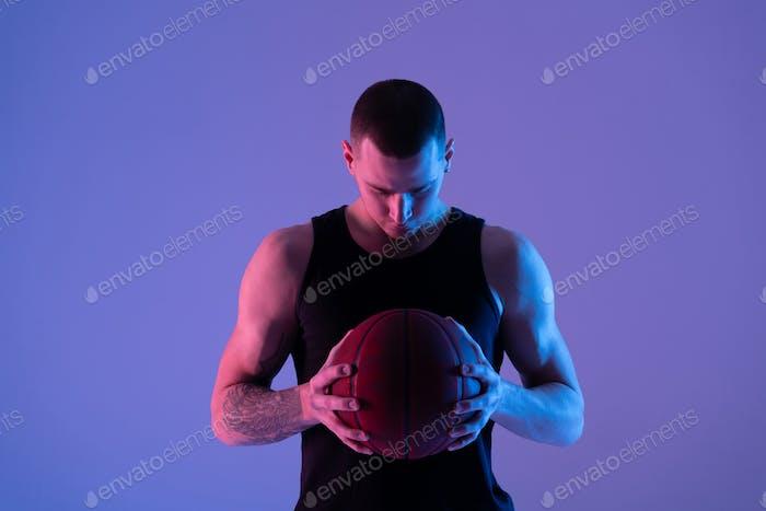Tattooed athlete with basketball ball under blue illumination