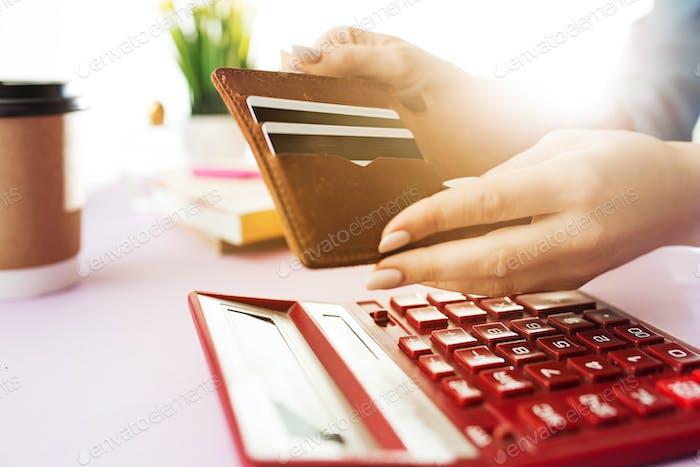 Frau hält Geldbörse, Kreditkarte in den Händen und die Berechnung der Kosten