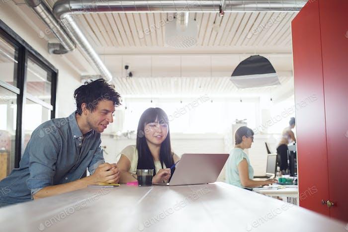 Mann und zwei Frauen arbeiten im Büro, Frau steht im Hintergrund durch Fenster