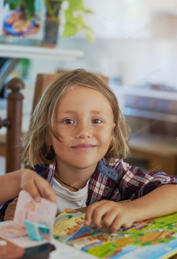 Joyful boy with books sits at table and looks at camera in room