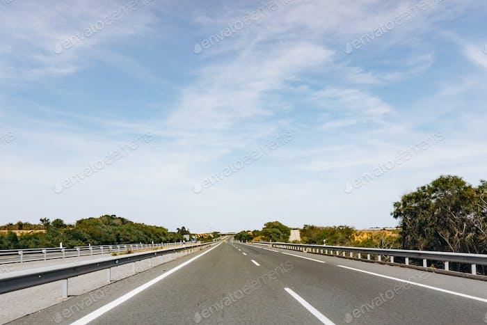 Asphaltstraße und schöne grüne Landschaft im Sommer