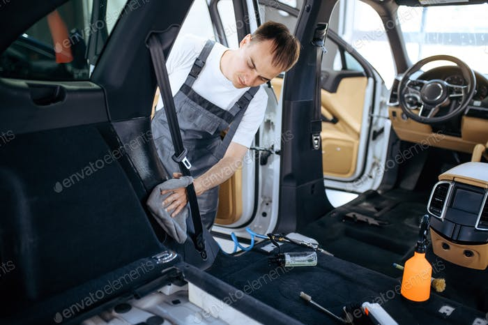 Worker with rag wipes car interior plastic