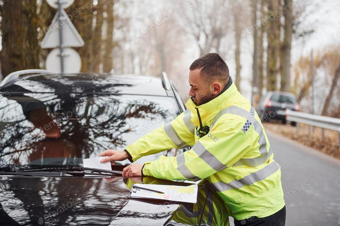Male police officer in green uniform putting fine list to the vehicle