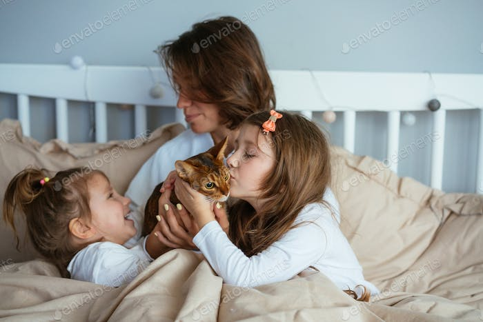 Happy mother and two daughters smiling hugs in bed