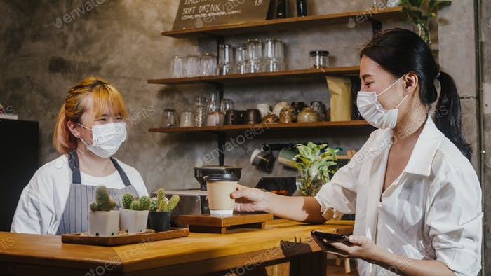 Young Asia female barista wear face mask serving take away hot coffee paper cup to consumer at cafe.