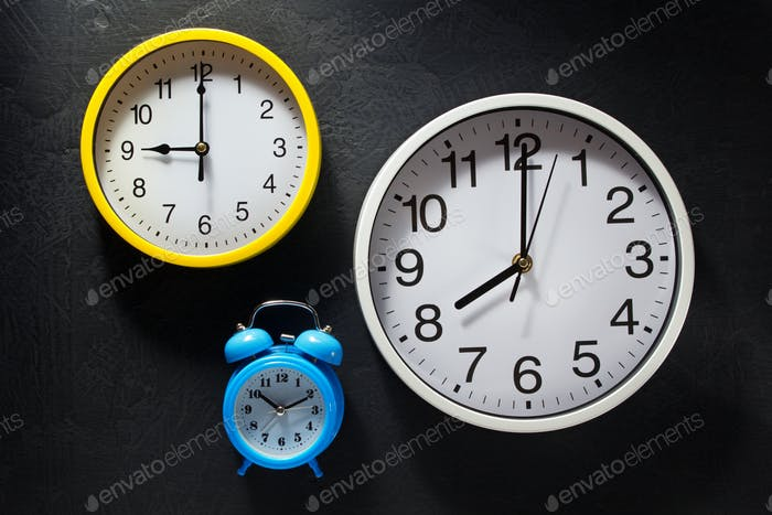 wall and alarm clock at black background