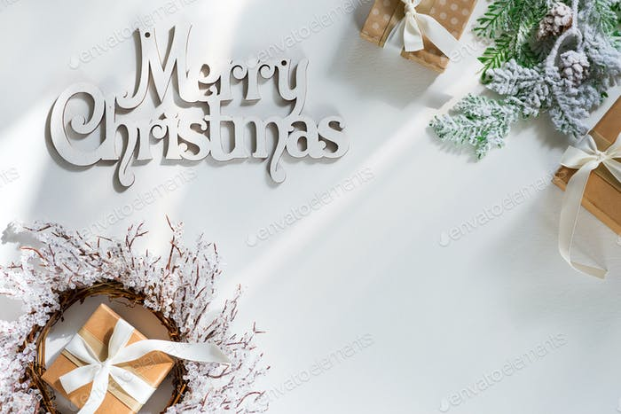 Gift boxes with snow fir branches, Wooden letters Merry Christmas and sunlight rays on a white