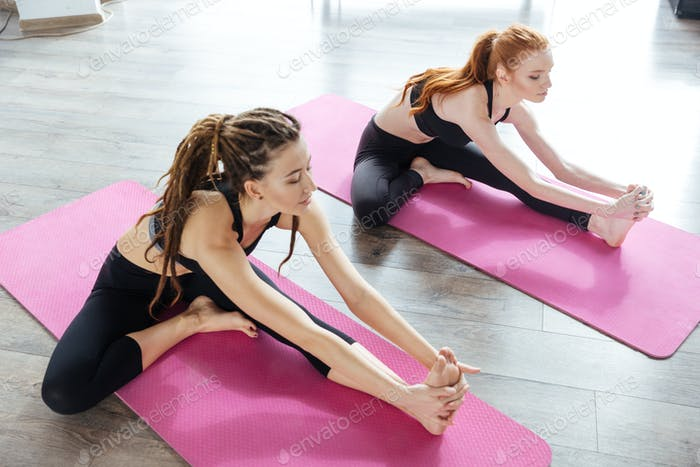 Two women stretching on the floor in yoga center