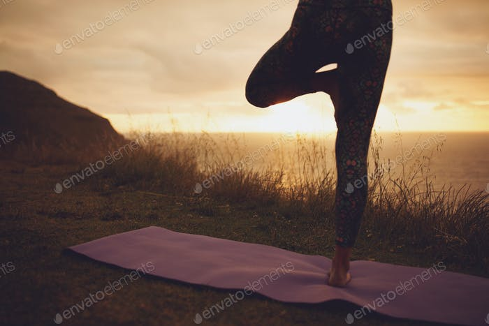 Woman practicing yoga on the cliff at sunset
