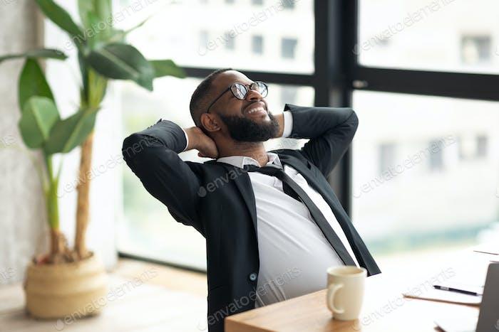 African American business man leaning back taking break