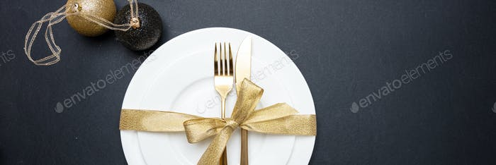 Table setting, xmas, new year. Gold cutlery on white set of dishes, black background