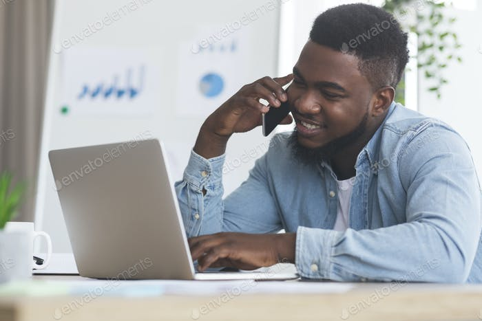 Employee talking on cellphone and working on laptop in office