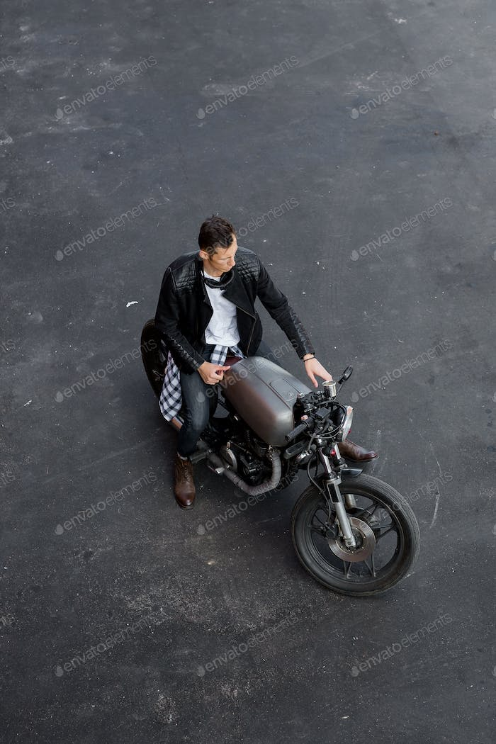 Top view to brutal man with cafe racer custom motorbike.