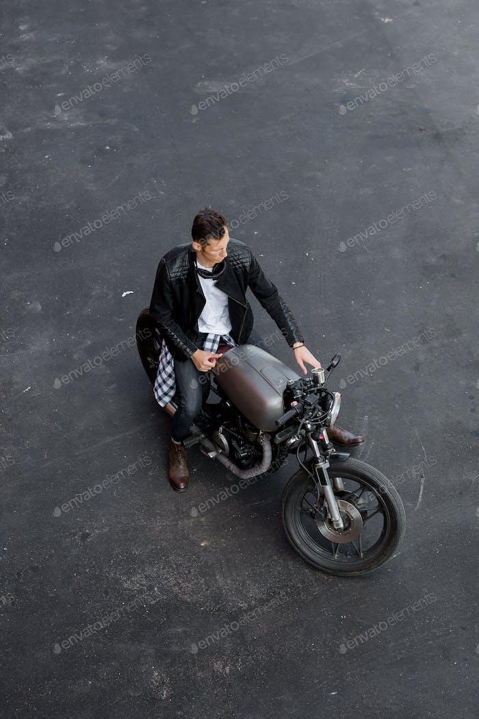 Vista superior al Hombre brutal con motocicleta personalizada cafe racer.