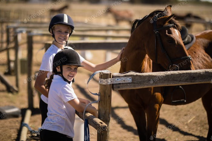 Smiling girls standing near the brown horse in the ranch
