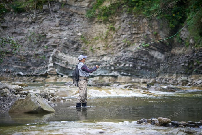 Competent fisherman hooking with rod in rough river