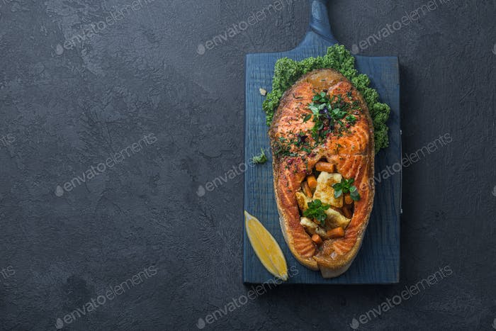 Tasty salmon steak with vegetables on wooden board, copy space
