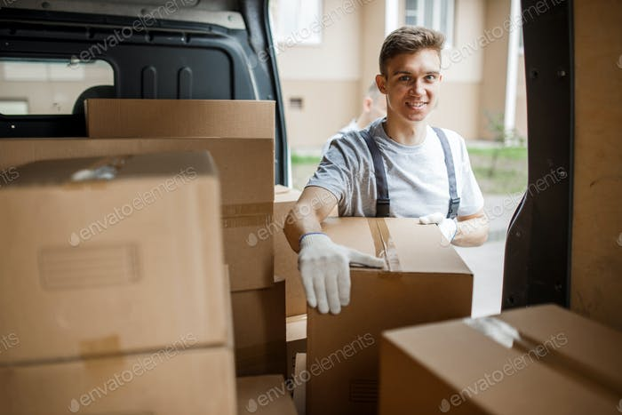 A young handsome smiling worker wearing uniform is standing next to the van full of boxes. House