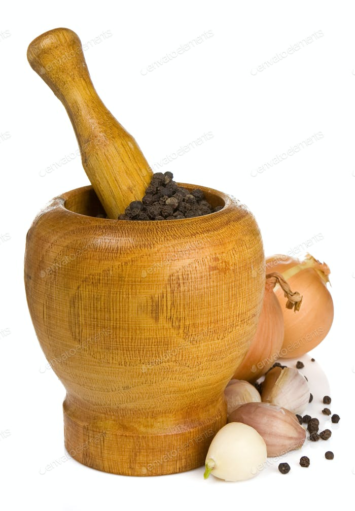 garlic, onion and pepper in mortar and pestle on white