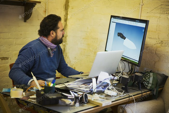 Bearded man sitting at a messy desk in a workshop, looking at a computer screen