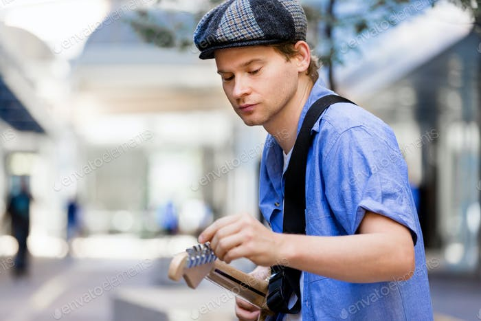 Young musician with guitar in city