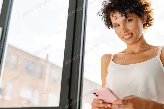 Smiling young curly woman standing