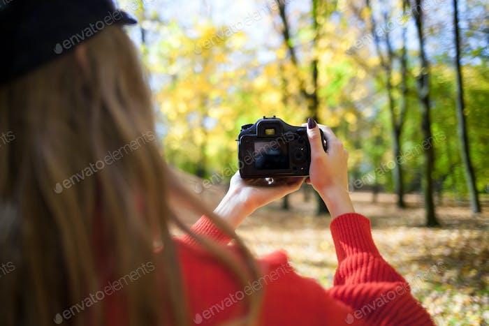 Woman making photos at green park, closeup on camera back screen