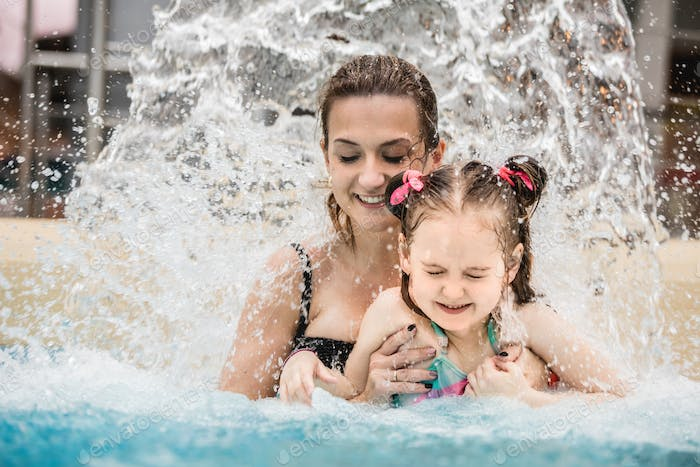 Woman and her daughter standing under a waterfall