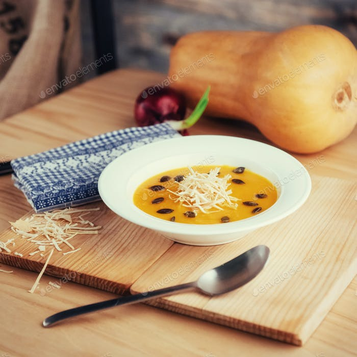 Pumpkin soup in white bowl, dietary vegetable