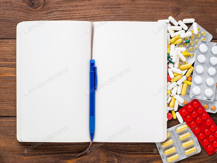 handful of scattered medicines, pills and tablets and note pad on brown wooden background