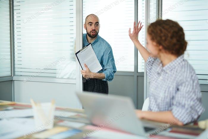 Verblüffte Assistentin mit Papieren ins Büro des Managers