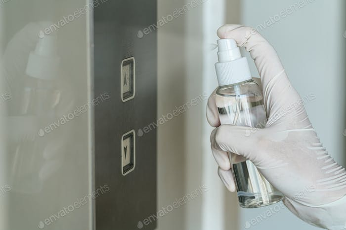 Closeup Asian woman hand wearing medical gloves and spraying Anti-Bacterial Sanitizer Spray