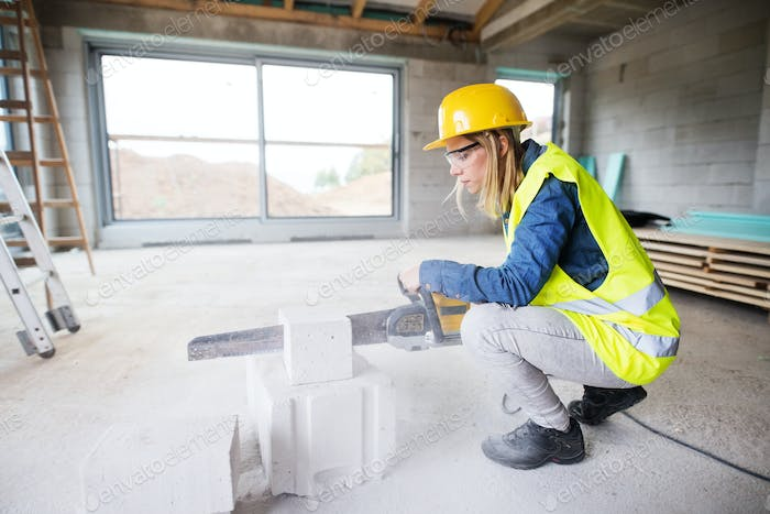 Young woman worker with saw on the construction site.