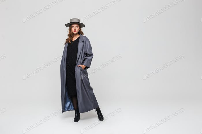 Young pensive woman with wavy hair and red lips in hat and cloak holding hands in pockets