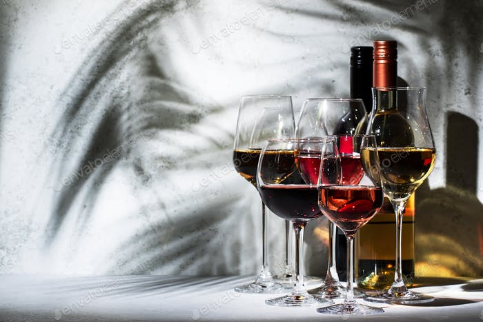 Red, white, rose wine in wineglasses on gray background. Wine tasting concept