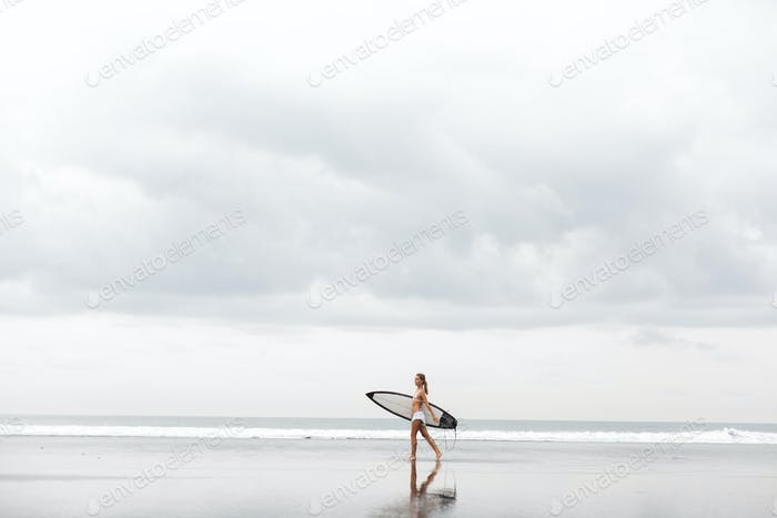 Thumbnail for teenage girl in a yellow bikini with her surfboard at a hawaii beach