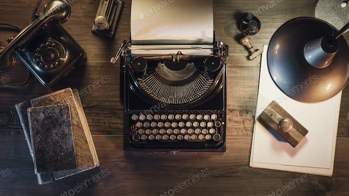 Vintage journalist desktop with typewriter and telephone