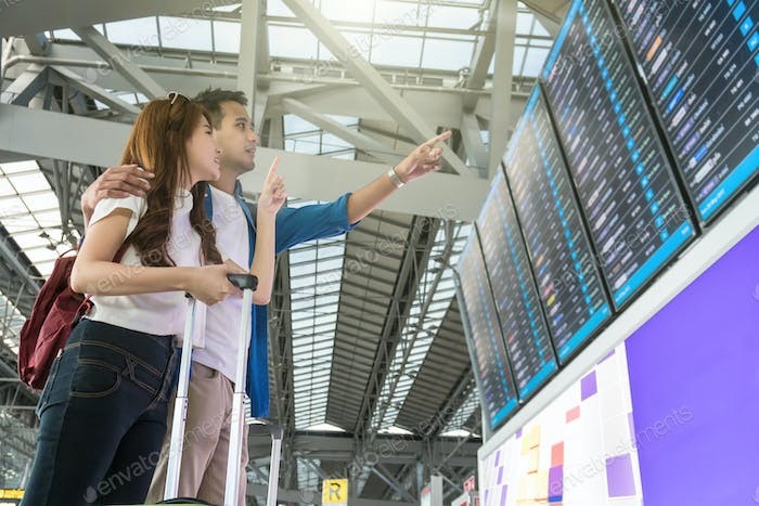 Asian woman traveler with suitcases pointing at the flight information screen