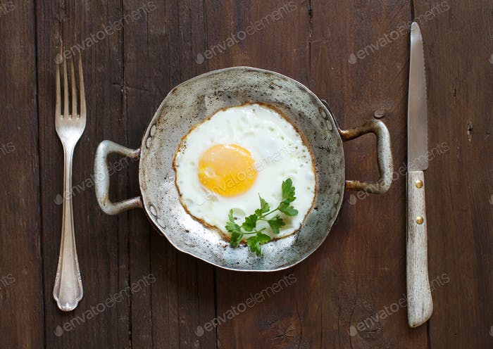 Fried egg in a old frying pan with fork and knife