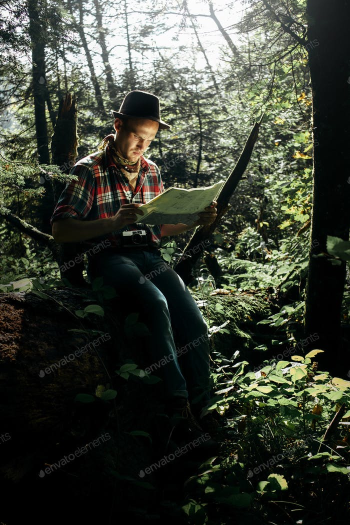 stylish hipster traveler exploring map with compass in sunny forest in the mountains