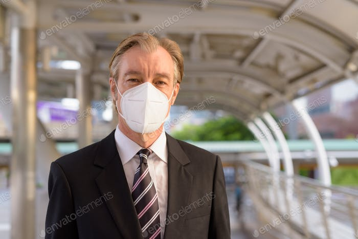 Face of mature businessman with mask for protection from corona virus outbreak at the footbridge