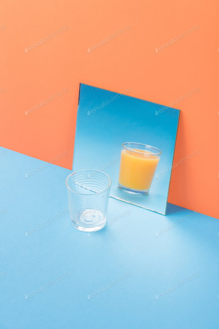 Glass on blue table isolated over orange background