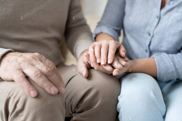 Hand of senior man in casualwear between those of his affectionate daughter